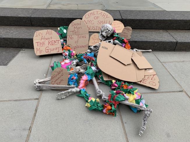 「小商業者保護法案」公聽會前,支持該法案的小商業團體在市政廳前集會呼籲通過該法案,並且擺出骷髏造型的道具,代表小商業者的艱難處境。(記者和釗宇/攝影)