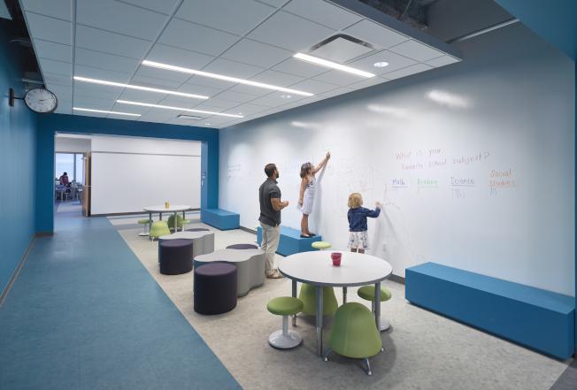 維州一所辦公室改裝成的新學校裡,低年級學童在白板上寫字。(美聯社)