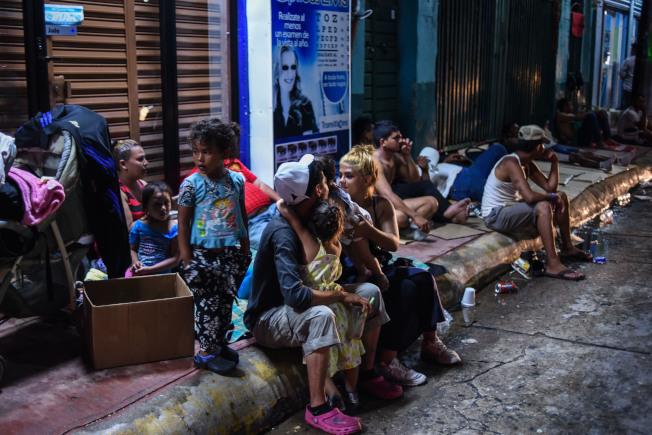 朝美墨邊界奔去的宏都拉斯移民23日在墨西哥Chiapas省的Huixtla市郊,全家在路邊休息。, 他們成群結隊一路步行,每天約行進六小時,未來行程還有1000公里。(Getty Images)