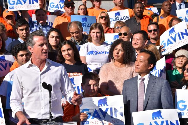 距11月6日投票日僅七天,加州州長候選人、現任副州長紐森(前左)10日上午9時,與妻子及支持者一起搭乘競選巴士來到舊金山市政廳正門,與金山選民見面並舉行造勢大會,爭取選民支持。 紐森的競選口號為「改變的勇氣」,宣示為加州帶來新面貌。他到市政大樓與支持他的民選官員及支持者做選前最後衝刺。 當天出席造勢大會的包括州眾議員邱信福、舊金山市長布里德、議長郭嫻、美國潮商會理事長林志斯等人士,共同支持紐森成為下一任州長。 州長選舉是今年加州最重要的選舉。最新民調顯示,紐森以54%比31%領先考克斯,領先幅度23個百分點。紐森不但民調領先,所籌到競選經費也比考克斯多10倍。(圖與文:記者周喆)