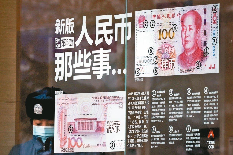 美國財長米努勤說,和大陸貿易談判將納入人民幣匯率問題。圖為北京一間銀行張貼的新版人民幣紙鈔說明。 (美聯社)