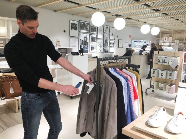 快時尚服飾店職員掃瞄衣服條碼查看庫存。(路透)