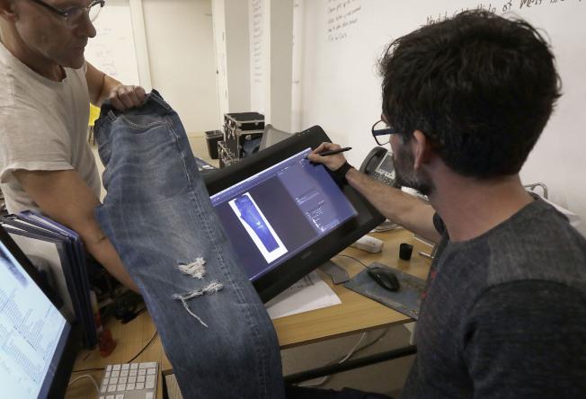 牛仔褲製造商員工正在討論牛仔褲的創意設計。(美聯社)