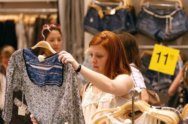 顧客在服飾店裡選購商品。(路透)
