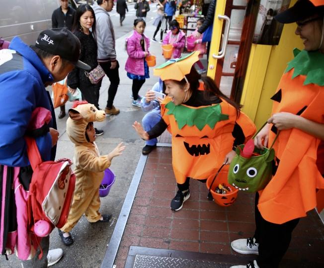 華埠雪糕行店員們穿著南瓜變裝,在店門口熱情招呼討糖兒童。(記者洪群超/攝影)