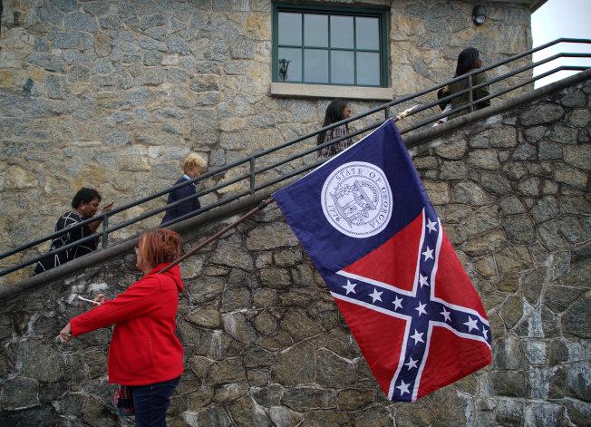 在民主黨州長候選人艾步蘭走進會場時,場外抗議者扛著老的喬治亞州旗,上面有著邦聯標誌。(路透)