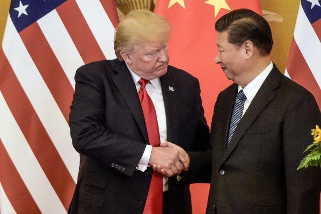 川習熱線通話,美中貿易戰似有轉圜跡象,圖為去年11月川普訪問北京,與習近平握手。(美聯社)