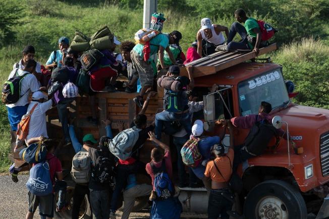 大部分是宏都拉斯人的「大篷車隊」移民,在墨西哥爬上一輛卡車,向美墨邊界進發。(Getty Images)