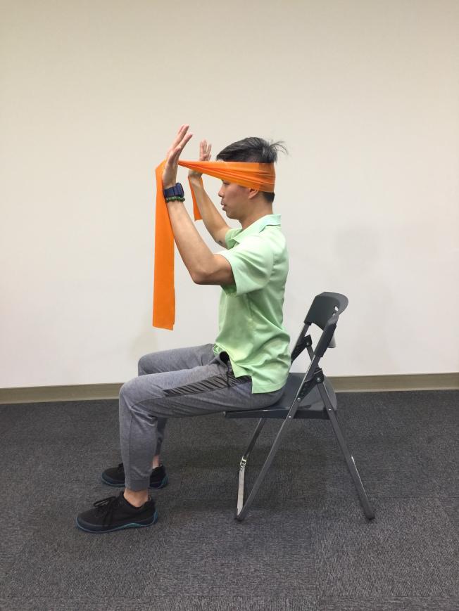 第四招:頸部後推 坐姿,雙手將彈力帶拉開,放在頭部後方。(記者陳雨鑫╱攝影)