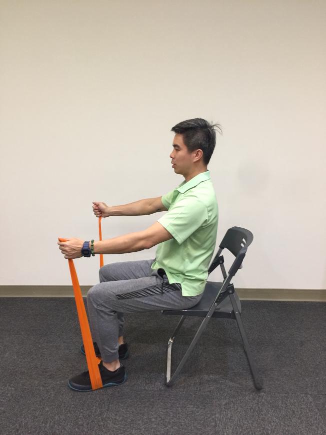 第三招:捲腹抖抖 坐姿,腳踩在彈力帶中間,雙手將彈力帶拉起。手肘向前伸直但不卡死,身體上挺。(記者陳雨鑫╱攝影)