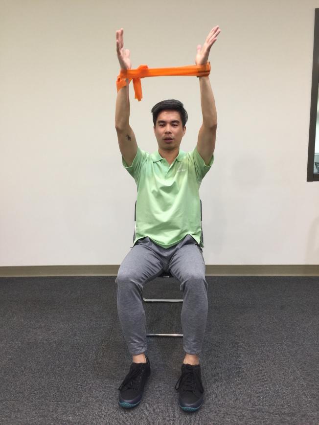 第五招:肩部上抬 坐姿,將彈力帶打個圈圈,雙手向外撐開。身體上挺,雙手在大腿的上方,再往上舉。(記者陳雨鑫╱攝影)