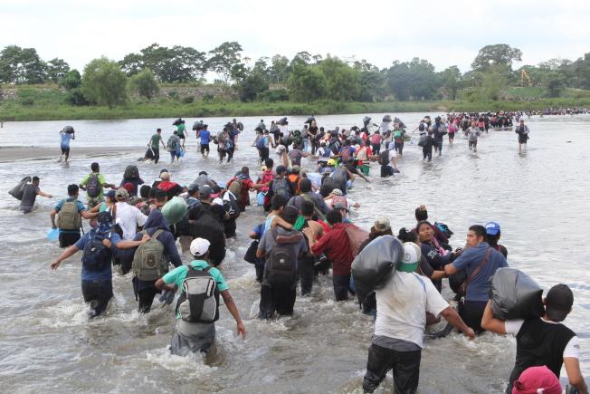 一波波中美洲移民繼續要進入墨西哥,朝美墨邊界進軍,試圖進入美國尋求政治庇護。這群瓜地馬拉移民扶婦攜幼,3日強行度過瓜墨兩國邊界蘇加特河, 進入墨國。(美聯社)
