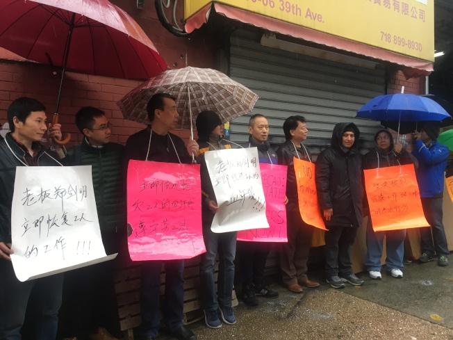 法拉盛勞工中心連同遭非法解雇員工,5日冒雨於鄭劍明店前舉牌抗議。(記者賴蕙榆/攝影)