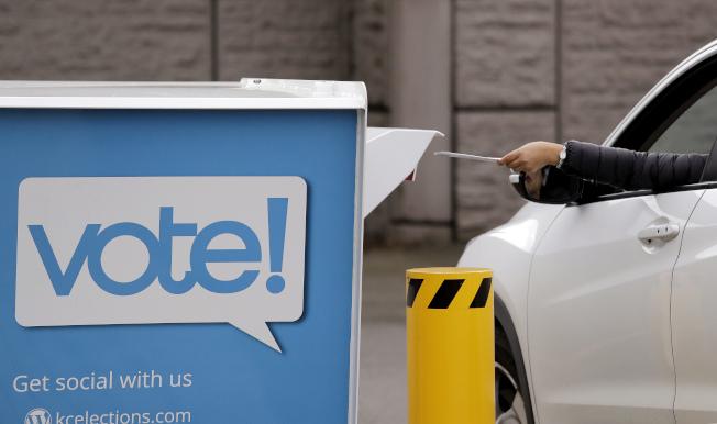 一位駕駛將選票投進箱子裡。(美聯社)