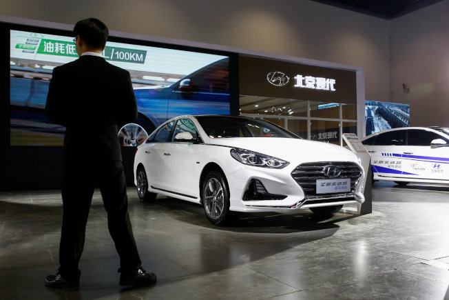 南韓車廠現代第三季獲利大幅下滑,原因是美中兩大海外市場業績欠佳。圖為一名男子站在中韓合資企業北京現代汽車展場一輛索納塔(Sonata)混合動力車旁。(路透)