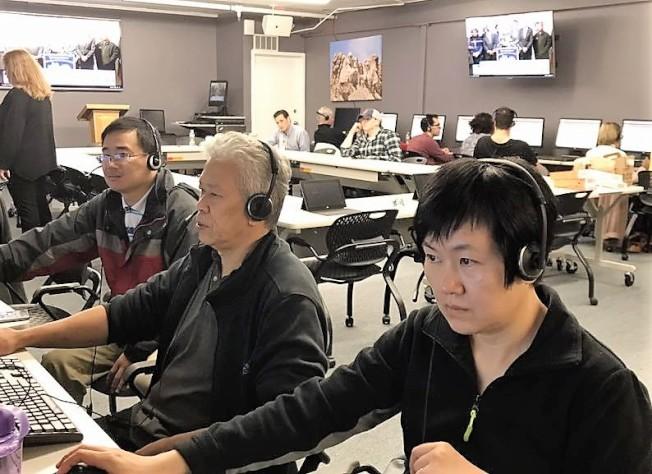 華洋義工6日在馮偉傑競選部電話中心與選民聯絡,積極為其拉票。(張剛提供)