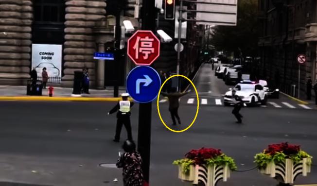 網上視頻顯示,疑似國家主席習近平的車隊經過上海黃浦區外灘中山東路口時,一名男子(圓圈處)突然衝出馬路,意圖攔截車隊,遭警員制伏。(視頻截圖)