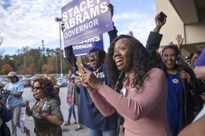 喬治亞州非洲裔州長候選人艾布蘭的支持者,在投票站前為她熱心拉票。(美聯社)