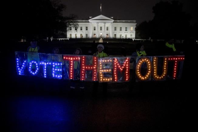 選前最後一夜,反川普團體在白宮前舉牌,要選民「用選票把他們趕出去」。(美聯社)