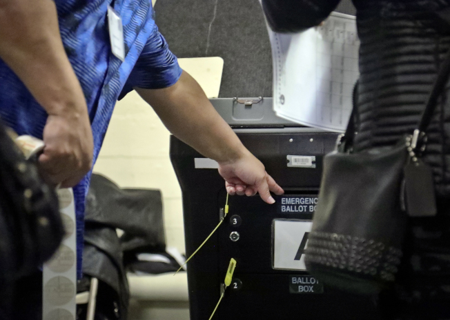 紐約市布朗士區一家投票所因投票人數太多,導致選票電腦掃瞄器故障,維修人員搶修,也造成投票選民大排長龍。(美聯社)