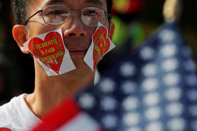 10月14日哈佛大學附近舉行的集會上,一位示威者臉上貼著口號貼紙。(路透)