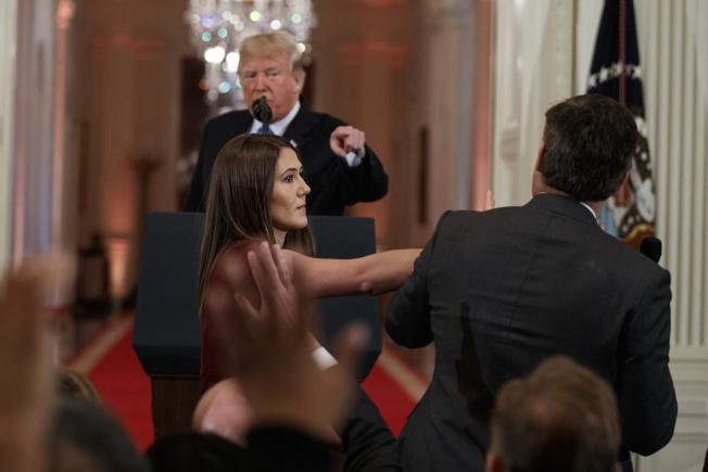 CNN記者阿科斯塔在白宮記者會上與川普當面爭執,白宮助理上前欲取回阿科斯塔的麥克風。(美聯社)