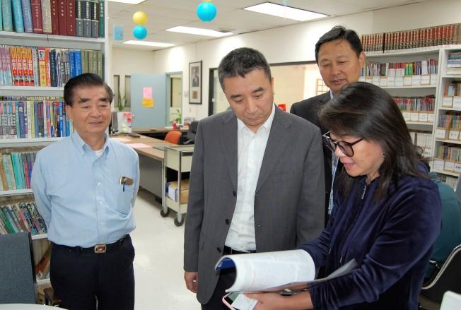 中國人活動中心辦公室主任周愛萍(右一)向王雲波部長(左二)介紹中心靳寶善圖書館的情況。(記者賈忠/攝影)