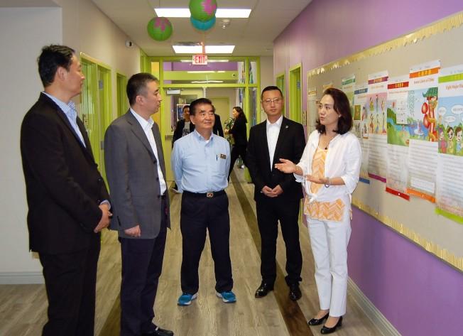 中國和平統一促進會海外部部長王雲波(左二)在騰龍教育學院聽取該校董事長俞曉春(右一)的介紹。(記者賈忠/攝影)