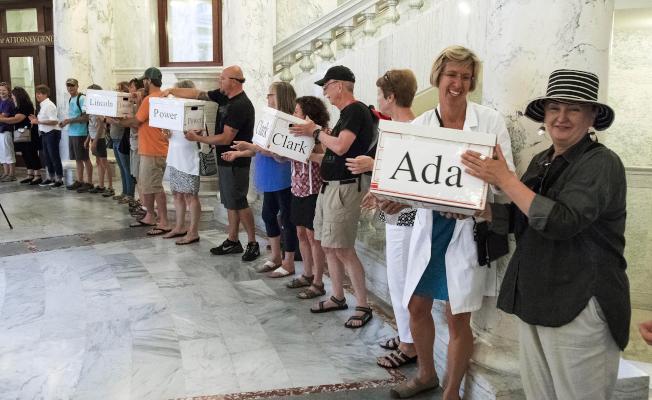 愛達荷州選民不顧共和黨控制的州議會反對,6日投票贊成擴大醫療補助計畫。圖為愛州民眾為擴大醫療補助計畫公投案收集簽名。(美聯社)