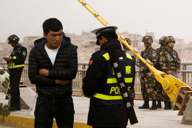 新疆「再教育營」議題引發國際對中國人權關切。圖為新疆一名男子去年在喀什市街頭遭警方盤查證件。(路透資料照片)