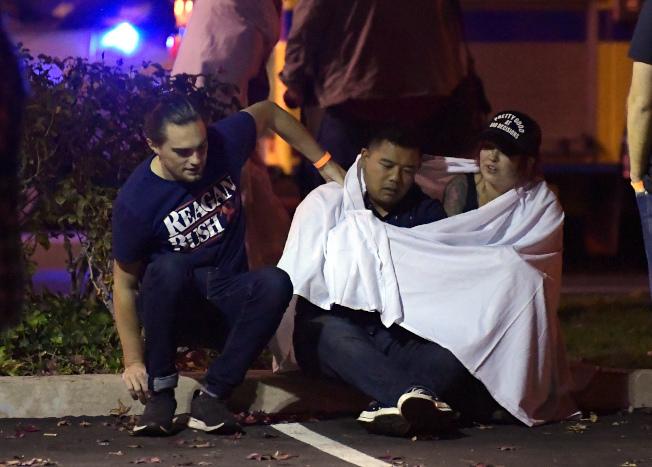 逃出現場的目擊者在安全區域互相安慰。(美聯社)