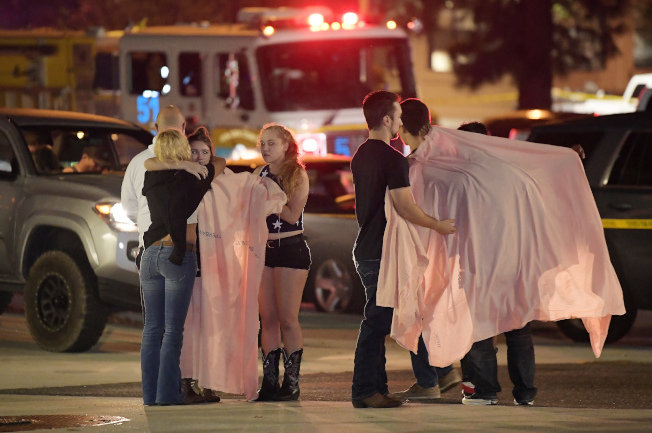 槍下餘生的倖存者在酒吧外面互相安慰。(美聯社)