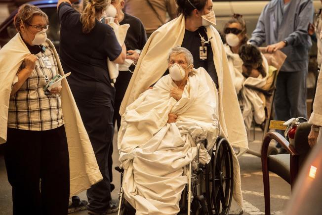 天堂市的一家医院被大火波及,医院的病人须紧急撤离。(美联社)