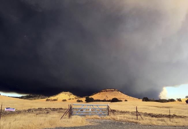 布特縣大火現場沖天而起的黑煙。(美聯社)