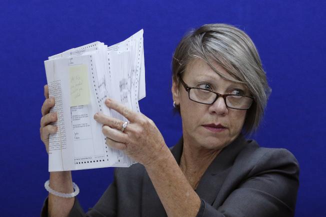 佛州布羅瓦郡選票監督委員會主席班森法官手持一些選票,準備仔細檢視。(美聯社)