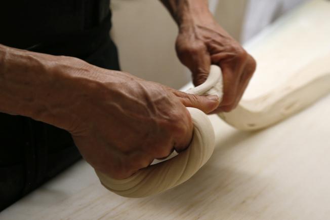 師傅必須經過數年才練就一番捏貝果麵糰的功夫。(美聯社)