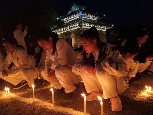 中國武俠有著兩千年傳統。圖為香港金庸迷穿著武俠服飾紀念金庸。(路透)