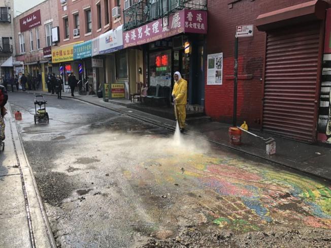 位於華埠的大型壁畫「龍與花之歌」日前展期結束,華埠商改區請來清潔人員以強力水柱清洗。(記者顏嘉瑩/攝影)