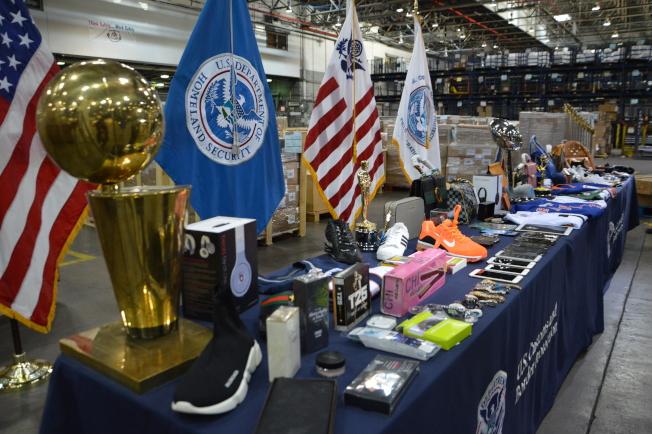 CBP工作人員展示名牌皮包、獎杯、仿冒三星及iPhone等智能手機以及耐吉球鞋等仿冒產品。(記者牟蘭/攝影)