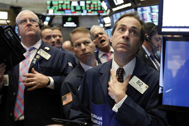 華爾街股市20日連續第二天大跌,掃盡2018年利得,紐約證交所內交易員心臟病都要發作了。(美聯社)