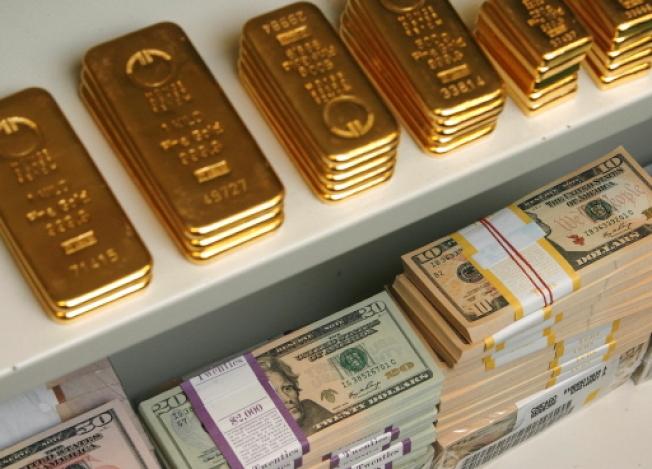 川普政府公布提案顯示,坐擁數百萬財產的富人給予繼承人免稅贈與時,將能擁有更大彈性。圖為金條與美鈔。(路透)
