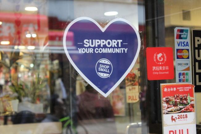 華埠商家在店門貼上標誌,參與「全國小商家星期六」。(記者張筠/攝影)