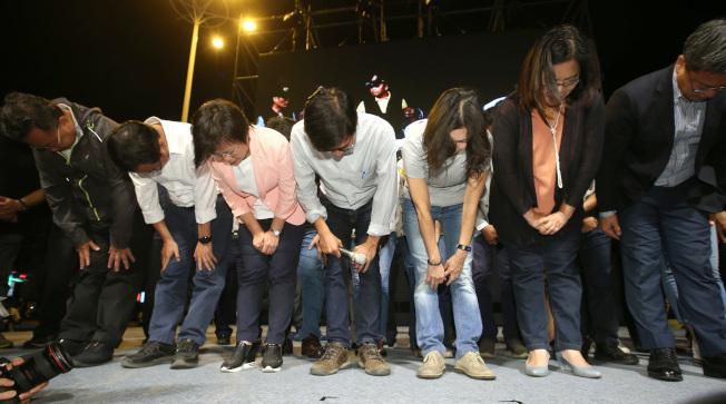 民進黨高雄市長候選人陳其邁(中)敗選,24日晚與競選團隊向支持者鞠躬表達感謝。(記者林澔一/攝影)