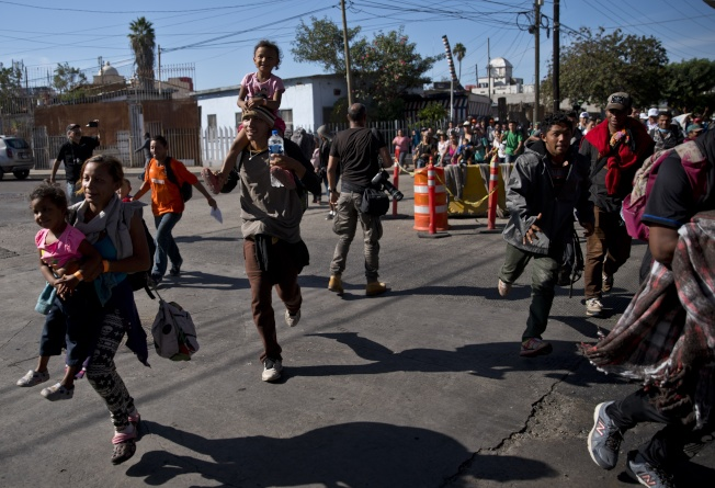 Central America Migrant Caravan Migrants run toward the U.S. after breaking past a line of Mexican police at the Chaparral border crossing in Tijuana, Mexico, Sunday, Nov. 25, 2018, near the San Ysidro, California entry point. More than 5,000 migrants are camped in and around a sports complex in Tijuana after making their way through Mexico in recent weeks via caravan.  (AP Photo/Ramon Espinosa)