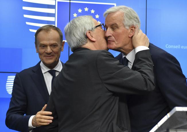 歐盟執行委員會主席榮科(中)在25日歐盟通過英國脫歐協議,大功告成,興奮地親吻歐盟英國脫歐首席談判代表巴尼耶(右)。(美聯社)