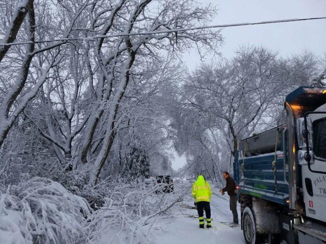 芝城北郊帕拉坦市(Palatine)路旁大樹的樹枝遭風雪吹斷橫在路中間,市府人員清理中。(讀者Joseph Qian提供)