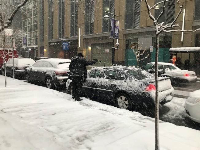 芝加哥市區民眾正在清理車上積雪。(記者董宇/攝影)