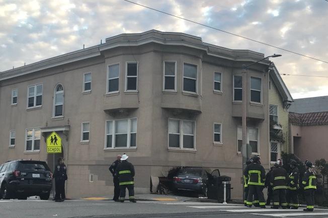 一輛汽車高速衝上日落區Taraval街與第24街交界路口的公寓大樓。(記者李秀蘭/攝影)