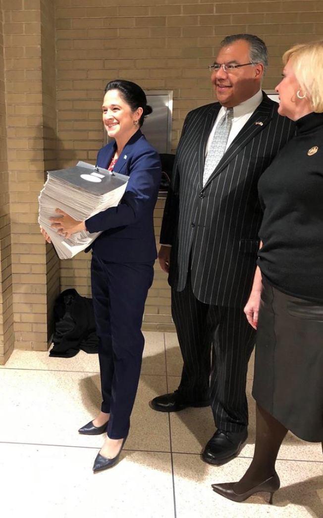 最晚宣布參選的現任伊州審計長曼多匝(左)日前捧著大疊選民連署名單到選委會繳交。(Marty Castro臉書截圖)