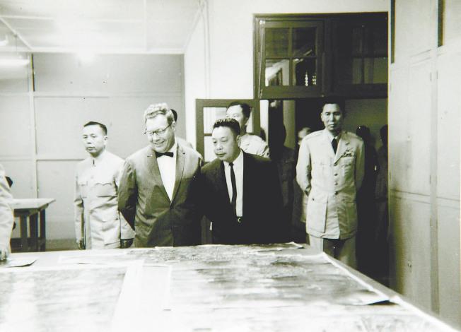 中華民國國防會議副秘書長蔣經國(前右)與中情局台北站站長克萊恩(前左),1961年11月觀看U-2偵察機拍回的空照圖。(報系檔案照片,國民黨黨史館提供)